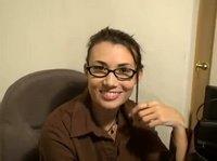 Брюнетка в очках ласкает себя сидя в креслице